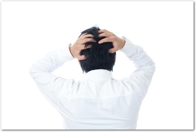 頭を抱える白シャツの男性の後ろ姿