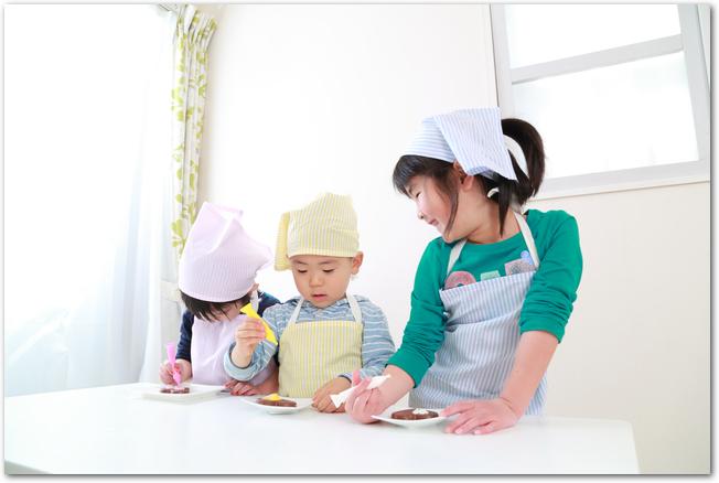 お菓子作りをするエプロン姿の子供たちの様子