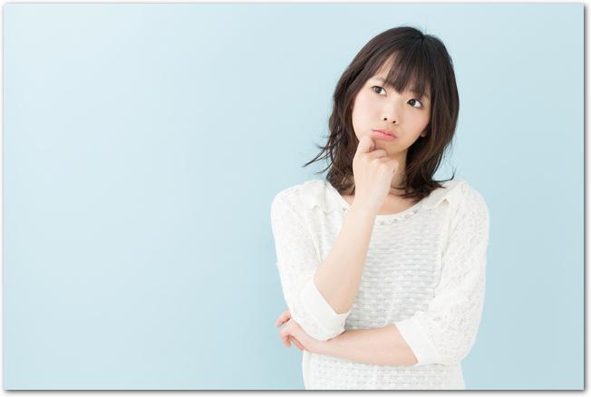 悩んだ表情を浮かべる若い女性