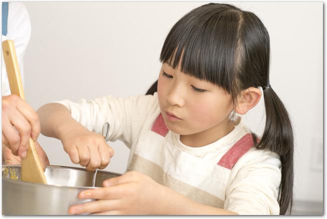 お菓子作りでボウルの中身を混ぜる女の子