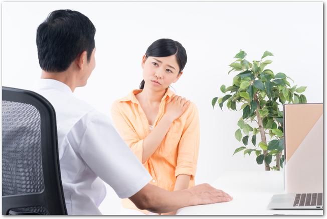 病院で問診を受ける肩こりで悩む女性