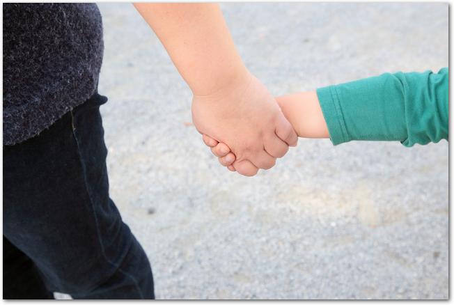 長袖Tシャツを着た子どもと母親が手を繋いでいる様子