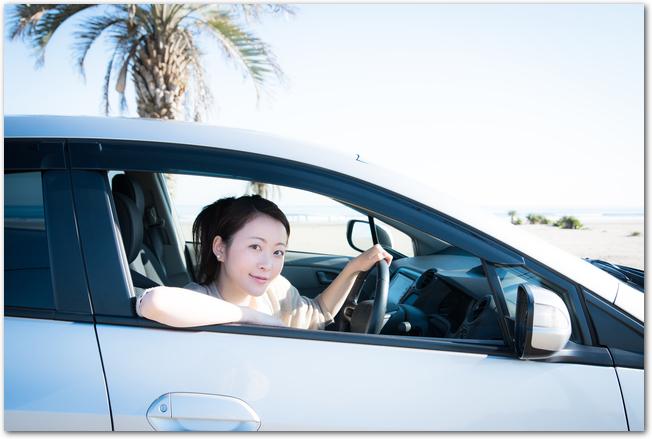 運転席から顔を出す沖縄をドライブ中の女性