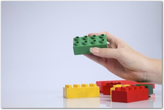 緑色のレゴブロックを持つ女性の手