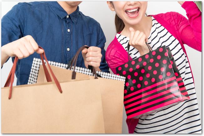 セールで買ったたくさんの紙袋を持つカップル