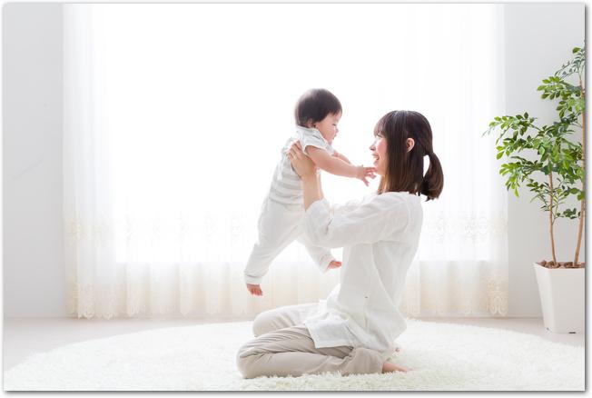 2歳の男の子を抱き上げる若い女性