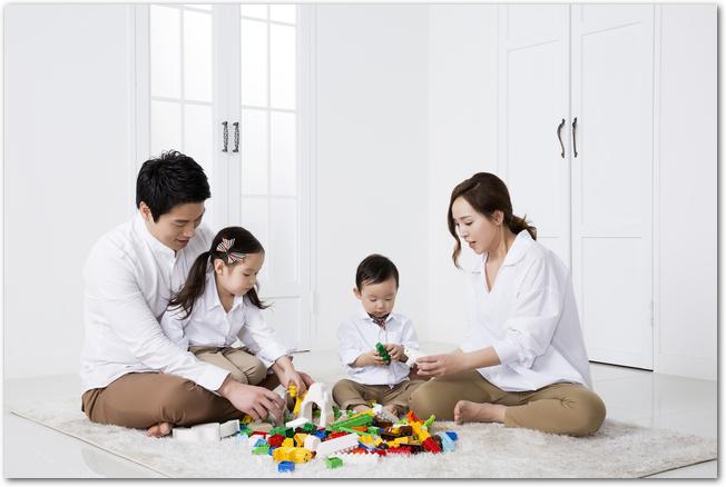 ラグの上でレゴブロックで遊ぶ両親と子どもたち