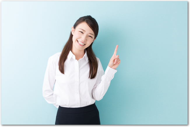 人差し指を立てる笑顔の若い女性の様子