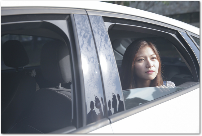 車の運転をする女性を後部座席から見た様子