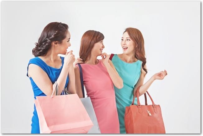 おしゃべりをしながら買い物を楽しむ若い女性3人組
