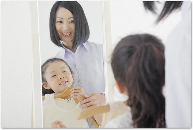 全身鏡の前で女の子に服を当ててみる母親の様子