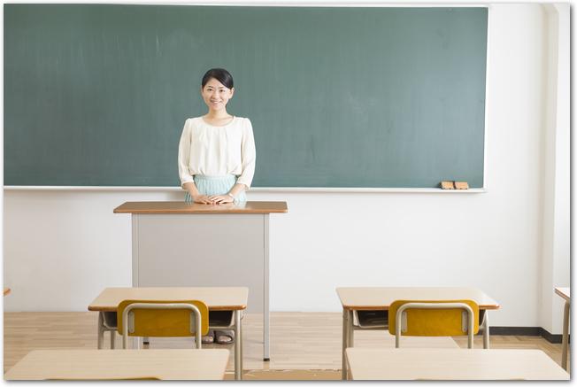 小学校の教室の黒板の前に立つ女性の先生