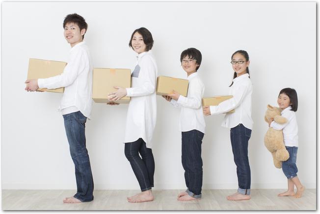引っ越しの段ボールを持つ5人家族の様子