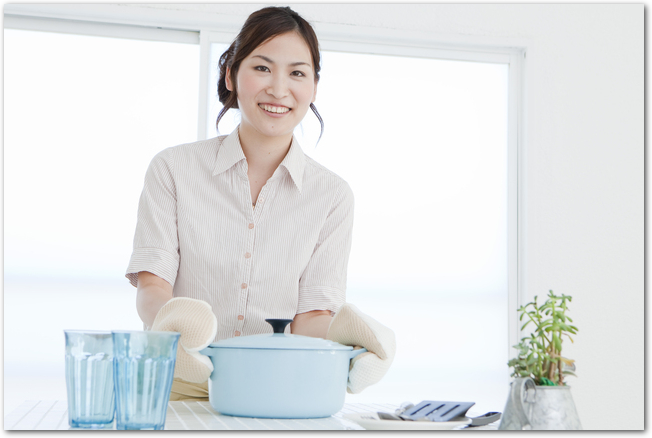 ル・クルーゼの鍋を持つキッチンで料理中の女性