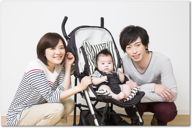 ベビーカーに乗っている赤ちゃんの両脇に座る笑顔の両親