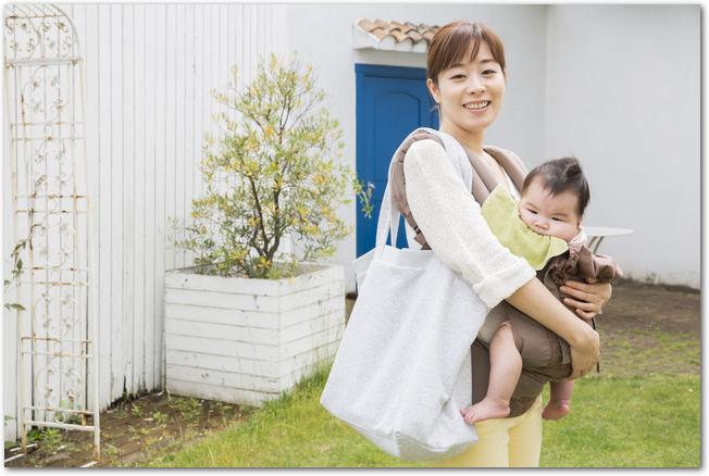 抱っこひもで母親に抱かれている男の子の様子