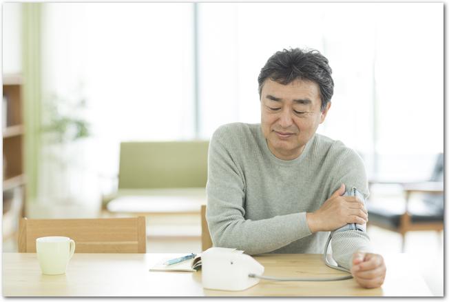 リビングで血圧を測るミドル男性