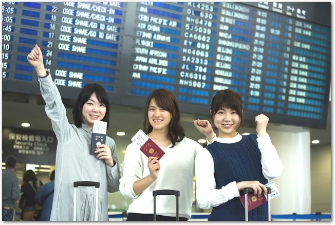 空港でパスポートを手にガッツポーズをする笑顔の3人組の女性