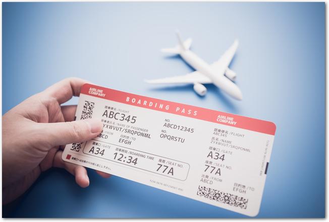 飛行機の模型の前で搭乗券を手に持っている様子