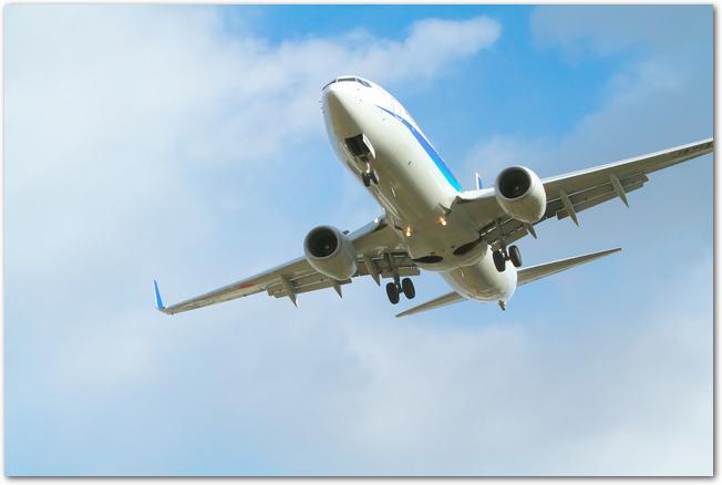 青空を飛ぶ旅客機の様子