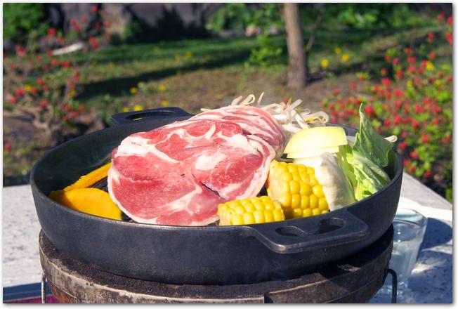 屋外で調理しているジンギスカン鍋の様子