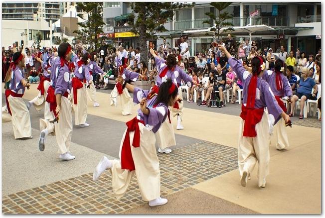 広場で鳴子を持って踊っているよさこいのチームの様子