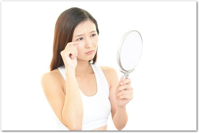 手鏡を見て不安げな表情を浮かべる女性の様子