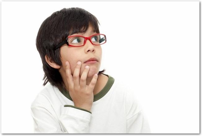頬に手を当てて斜め上を見る赤縁メガネの少年