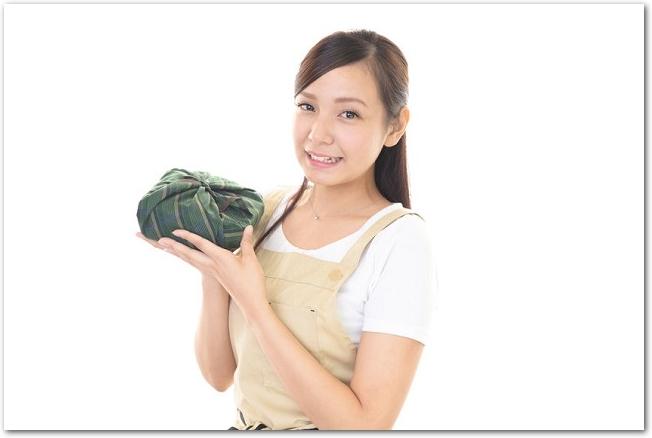 布に包まれたお弁当を持つ笑顔の女性の様子