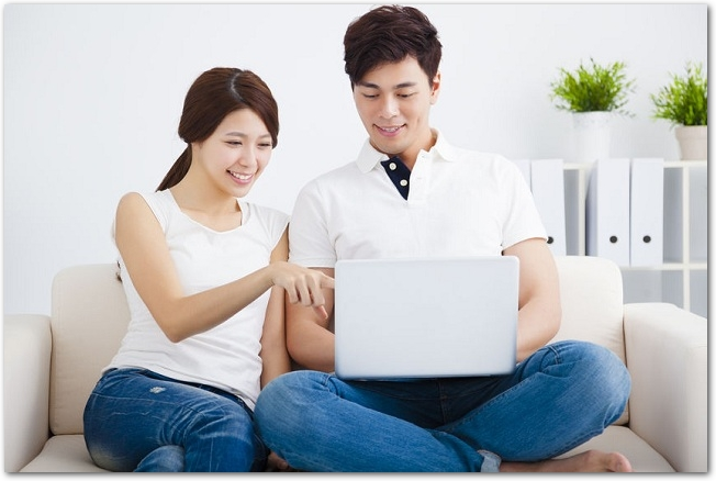 ソファーでノートパソコンを見ている夫婦の様子
