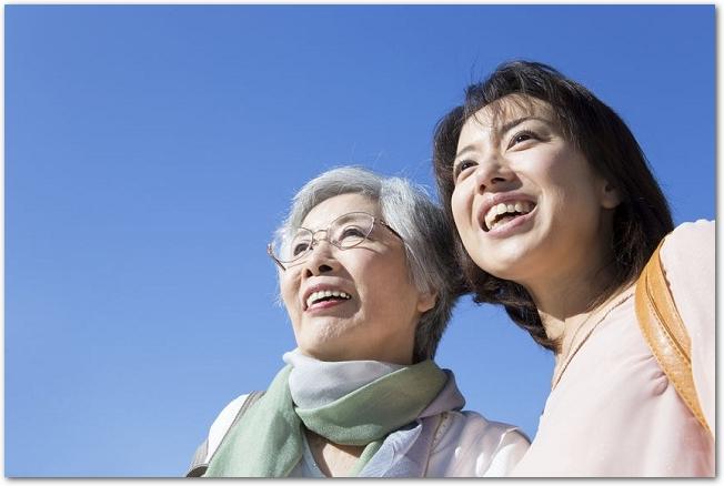 青空の下で笑顔を浮かべる娘と白髪の母親