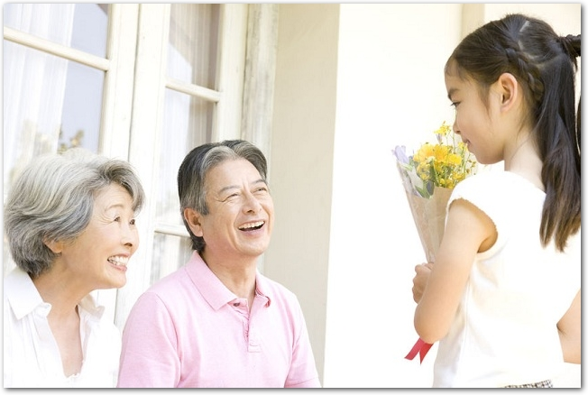 祖父母に花束を渡そうとしている孫娘の様子