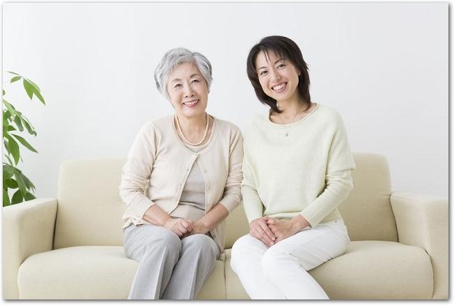 ソファーに並んで座っている笑顔の女性とシニア女性の様子
