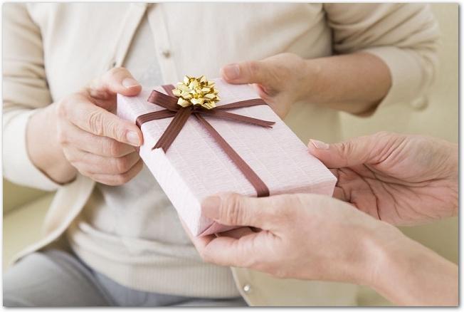 シニア女性にプレゼントが手渡されている様子