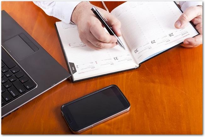 スマホとパソコンの横で手帳に書き込みをしている手元の様子
