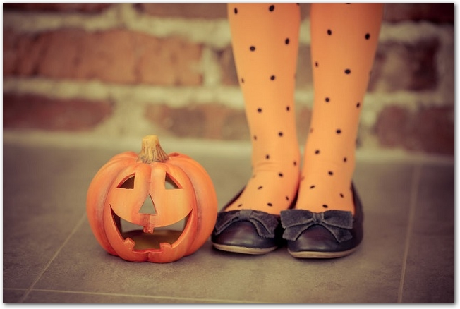 地面に置かれたジャックオランタンのカボチャと女性の足元