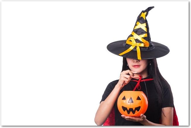 帽子で顔の上半分を隠したハロウィンで魔女のコスプレをしている女性