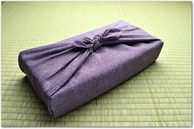 畳に置かれた紫色の風呂敷包み