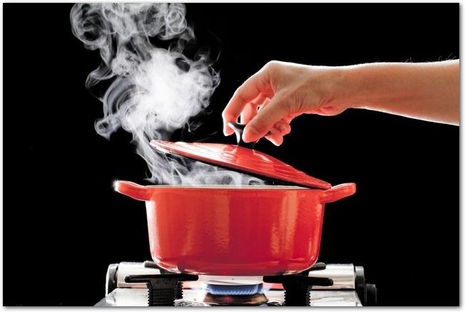ふたを開けた間から湯気が出ているカセットコンロにかけられた鍋