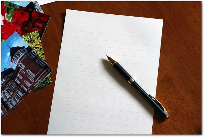 テーブルの上に置かれた写真と白紙の便箋とペン
