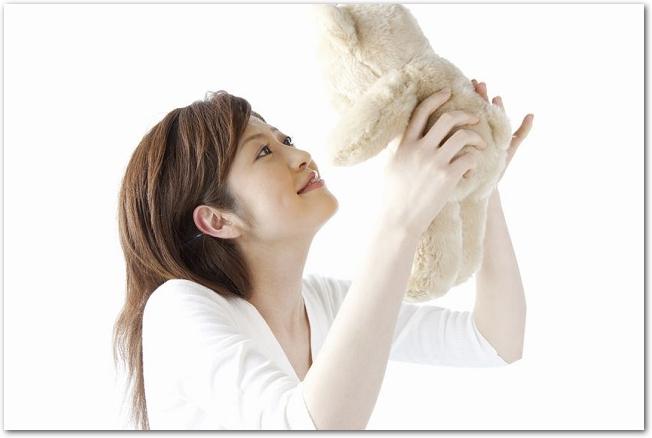 クマのぬいぐるみを持ち上げている女性の様子