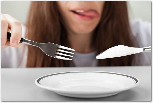 空のお皿の上でカトラリーを持つ空腹の女性の様子