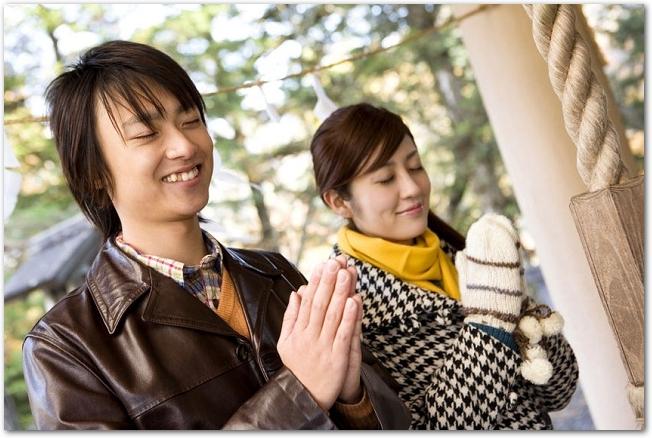 神社に初詣で参拝をしているカップルの様子