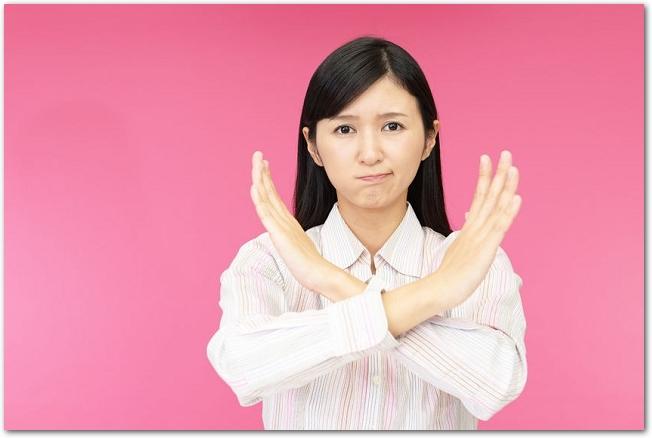 両手でバツ印を作って怒った表情を浮かべる女性の様子