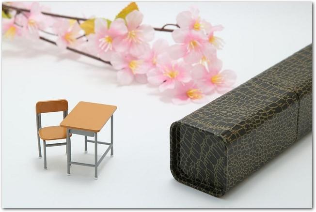 卒業証書の筒と桜の枝とミニチュアの机
