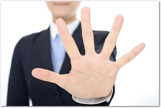 左手を突き出して拒否するポーズをしている様子