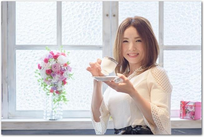 花を飾った窓辺でコーヒーを飲む笑顔の女性の様子