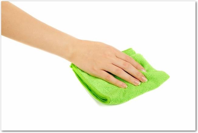 緑色の雑巾を持つ女性の左手