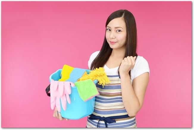バケツに入った掃除用具を持つエプロン姿の女性の様子
