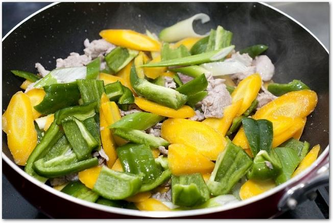 フライパンに入っているピーマンと豚肉の野菜炒め